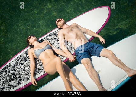Overhead view of young couple sunbathing on paddleboards - Stock Photo