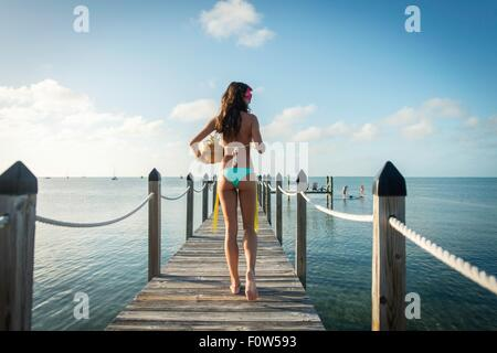 Rear view of young woman on sea pier carrying bowl of fruit, Islamorada, Florida, USA - Stock Photo