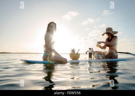 Two young women preparing cocktails on paddleboard, Islamorada, Florida, USA - Stock Photo