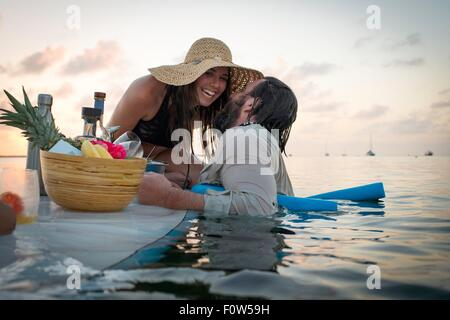 Romantic couple preparing cocktails on paddleboard, Islamorada, Florida, USA - Stock Photo