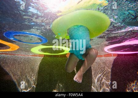 Underwater shot of girl kicking legs in swimming pool learning to swim with rubber ring - Stock Photo