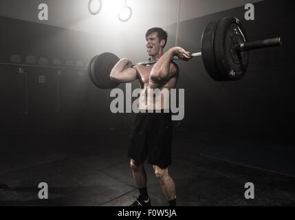 Mid adult man lifting barbell - Stock Photo