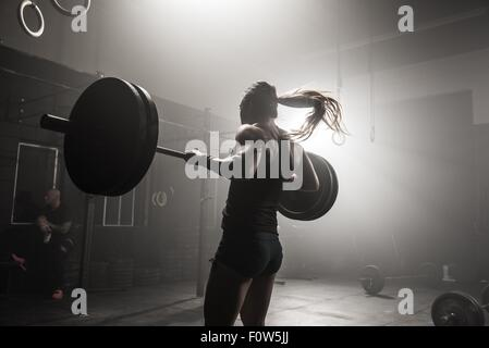 Young woman lifting barbell in gym, rear view - Stock Photo