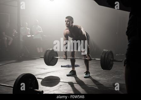 Young man lifting barbell - Stock Photo