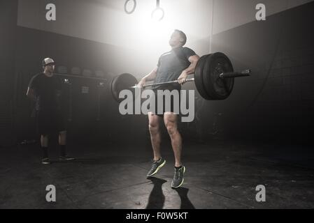 Young man lifting barbell while trainer looks on - Stock Photo