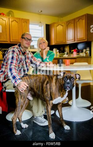 Couple sitting at dining table with boxer dog - Stock Photo