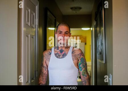 Portrait of mid adult man with tattoos wearing vest - Stock Photo