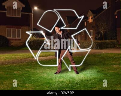Artist light painting a recycling symbol in park - Stock Photo