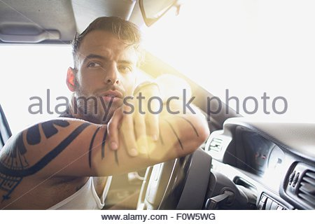 Young man arms crossed leaning against steering wheel - Stock Photo