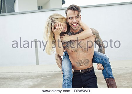 Young man giving young woman piggy back - Stock Photo