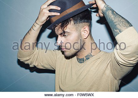 Young tattooed man putting on hat, looking away - Stock Photo
