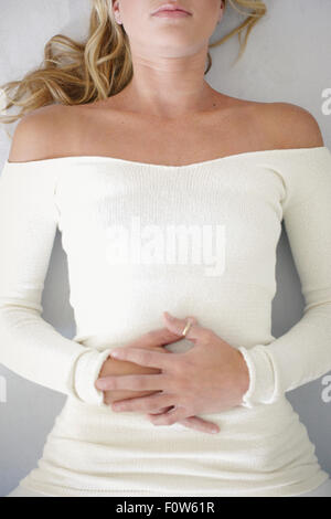 A blonde woman, in a white leotard lying on her back, her hands folded across her stomach, relaxing. - Stock Photo