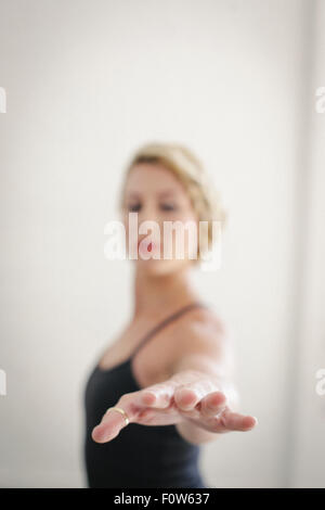 A blonde woman in a black leotard standing in a room, doing yoga, her arm outstretched. - Stock Photo