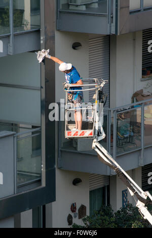 Workman on an elevated mechanical platform - Stock Photo