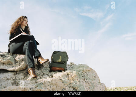 A woman sitting on a rock, writing in a notebook, a backpack lying by her feet. - Stock Photo