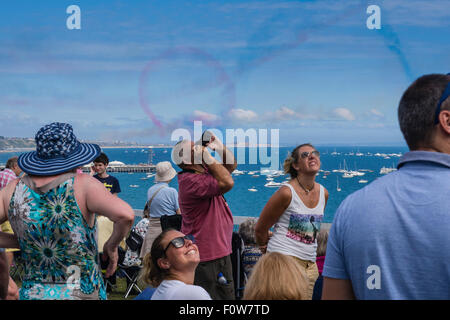 People on Clifftop watching the Red Arrows Display Team perform aerobatics above Poole Bay, Bournemouth, England, - Stock Photo
