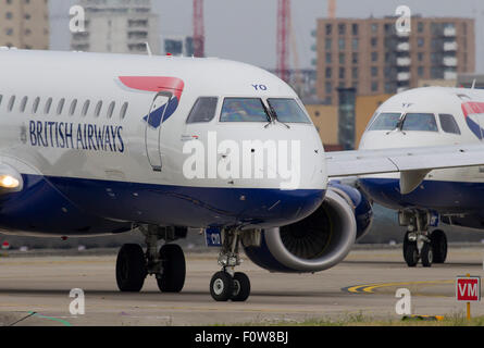 A British Airways BA CityFlyer Embraer ERJ-190 registration G-LCYO taxis for take off followed by Embraer ERJ-170 - Stock Photo