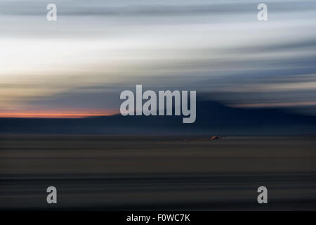 Car lights crossing a bumpy road on the steppes at dawn, near Khovd, Western Mongolia - Stock Photo