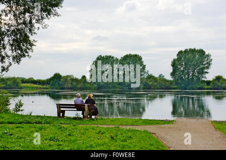 Mature couple sitting on bench overlooking lake, St Chad's Water off Wilne Rd, Derby Stock Photo