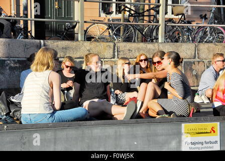 Young people enjoying themselves on the banks of the harbor and canals of Copenhagen, Denmark - Stock Photo