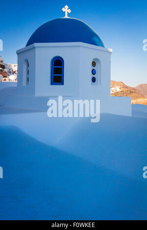 Iconic blue domed chapel in the town of Oia on the greek island Santorini (Thera) - Stock Photo