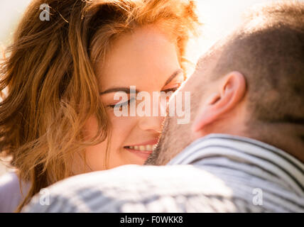 Candid close up photo of man kissing young smiling woman - Stock Photo