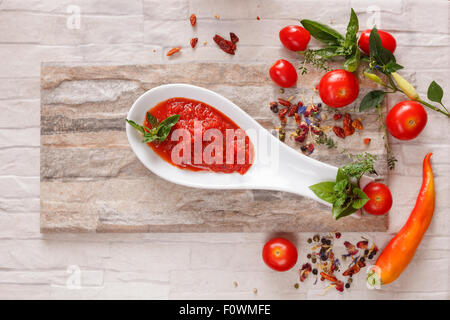 Tomato chutney with ingredients. Tomato and roasted pepper chutney on spoon, top niew - Stock Photo