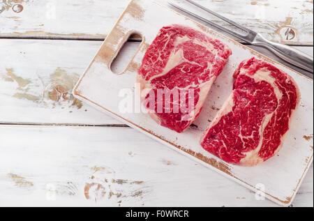 Raw fresh meat Ribeye Steak on white wooden  background. Top view - Stock Photo