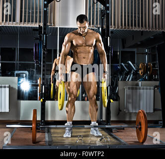 very brawny guy bodybuilder,  execute exercise with  weight - Stock Photo