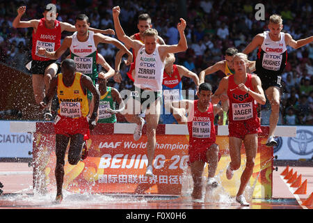 Beijing, China. 22nd Aug, 2015. Athletes in the Men's 3000 m Steeplechase Heats (1st Heat) cross a hurdle during - Stock Photo