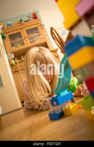 Little girl 5 year old playing indoors - Stock Photo