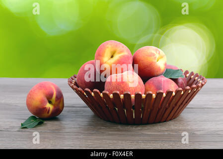 Ripe peaches at basket on table over green - Stock Photo