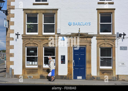 Elderly couple walking past Barclays Bank in the village of Helmsley, North Yorkshire, England. - Stock Photo