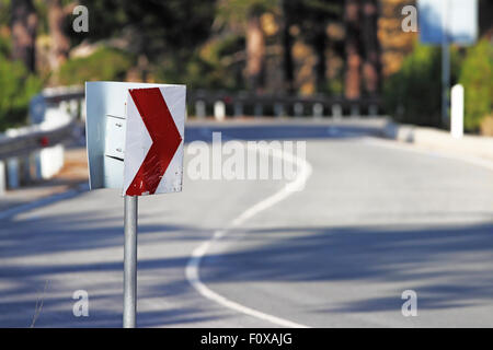 Right hand turn sign on the mountain road. Focus on the road sign. Troodos, Cyprus - Stock Photo