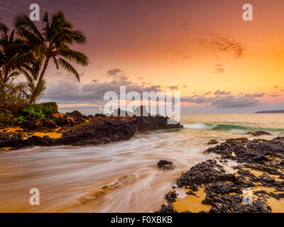 Beautiful secluded beach in Maui Hawaii at sunrise with palm tree lined lava rock foreshore and sandy beach. - Stock Photo