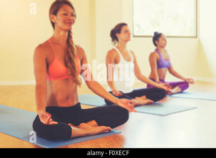 Group of People Relaxing and Meditating in Yoga Class. Wellness and Healthy Lifestyle. Shallow Depth of Field. - Stock Photo