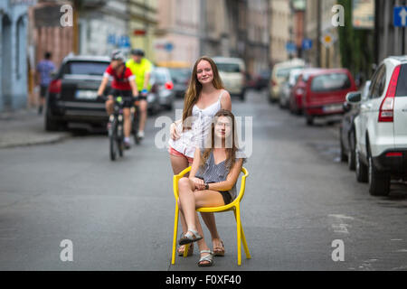Teenage girls in the street of the old town. One girl sits on the chair on the road, the second girl was behind - Stock Photo
