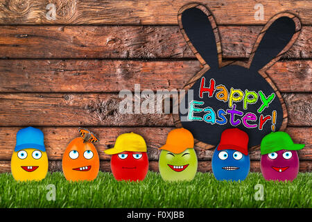 funny eater eggs in front of wooden easter background - Stock Photo