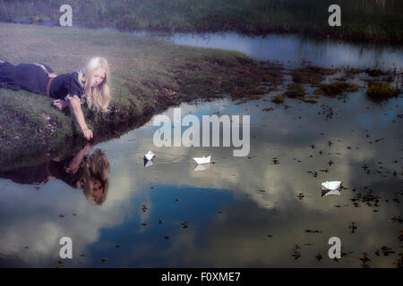 a girl with three paper boats on a pond - Stock Photo