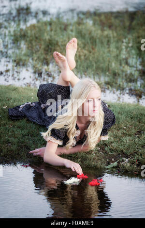a blond girl is placing flowers on a pond