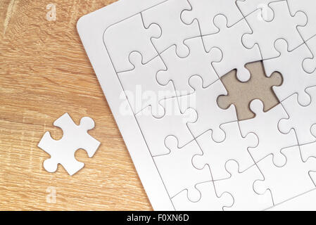 Piece missing from jigsaw puzzle as copy space placed on top of old wooden oak table, top view - Stock Photo