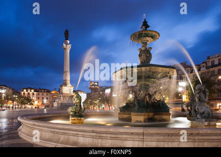 Portugal, Lisbon, Rossio Square by night in city centre with Baroque fountain and Column of Dom Pedro IV - Stock Photo