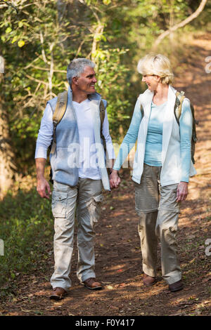 loving mid age couple walking in the forest and holding hands - Stock Photo