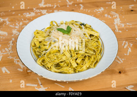 Tagliatelle pasta with pesto sauce and basil leafs on white plate, wood background - Stock Photo