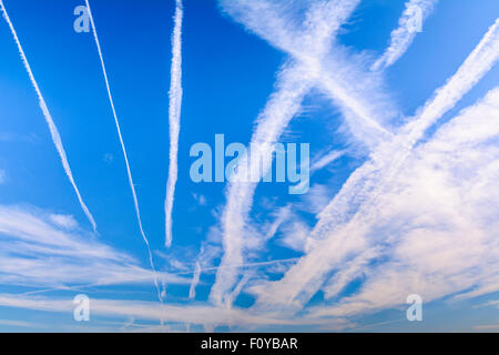 Condensation vapour trails (contrails) from jet engines on aircraft, in blue sky. Aeroplanes or airplane pollution. - Stock Photo