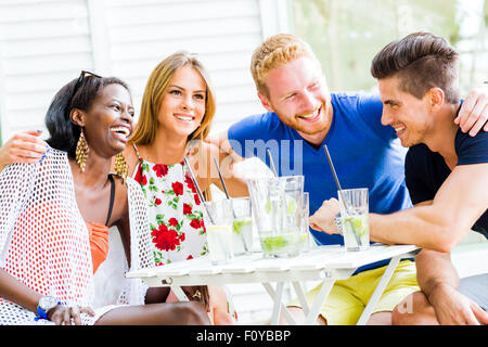 Friends laughing and hugging each other outdoors and being happy - Stock Photo