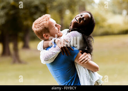 Portrait of a happy couple dancing and hugging in a park outdoors - Stock Photo