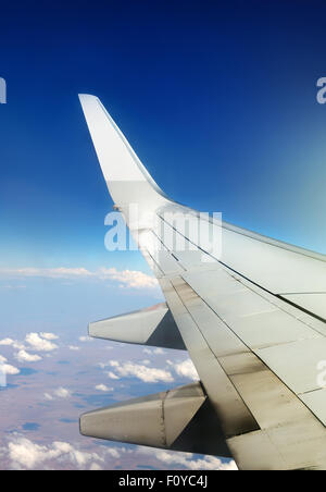 Wing of plane in sky and white clouds - Stock Photo