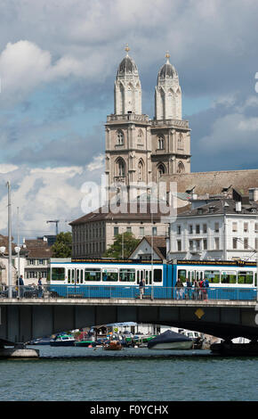 Panoramic view of Zurich, seen from the lake, with Grossmunster in the back and a 'tram' streetcar passing Quai - Stock Photo
