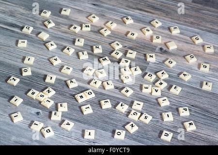 Plastic letter tiles scattered on wooden floor - Stock Photo